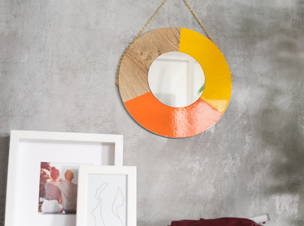 Round DIY wall mirror in color combinations made from adhesive film, hung on a chain